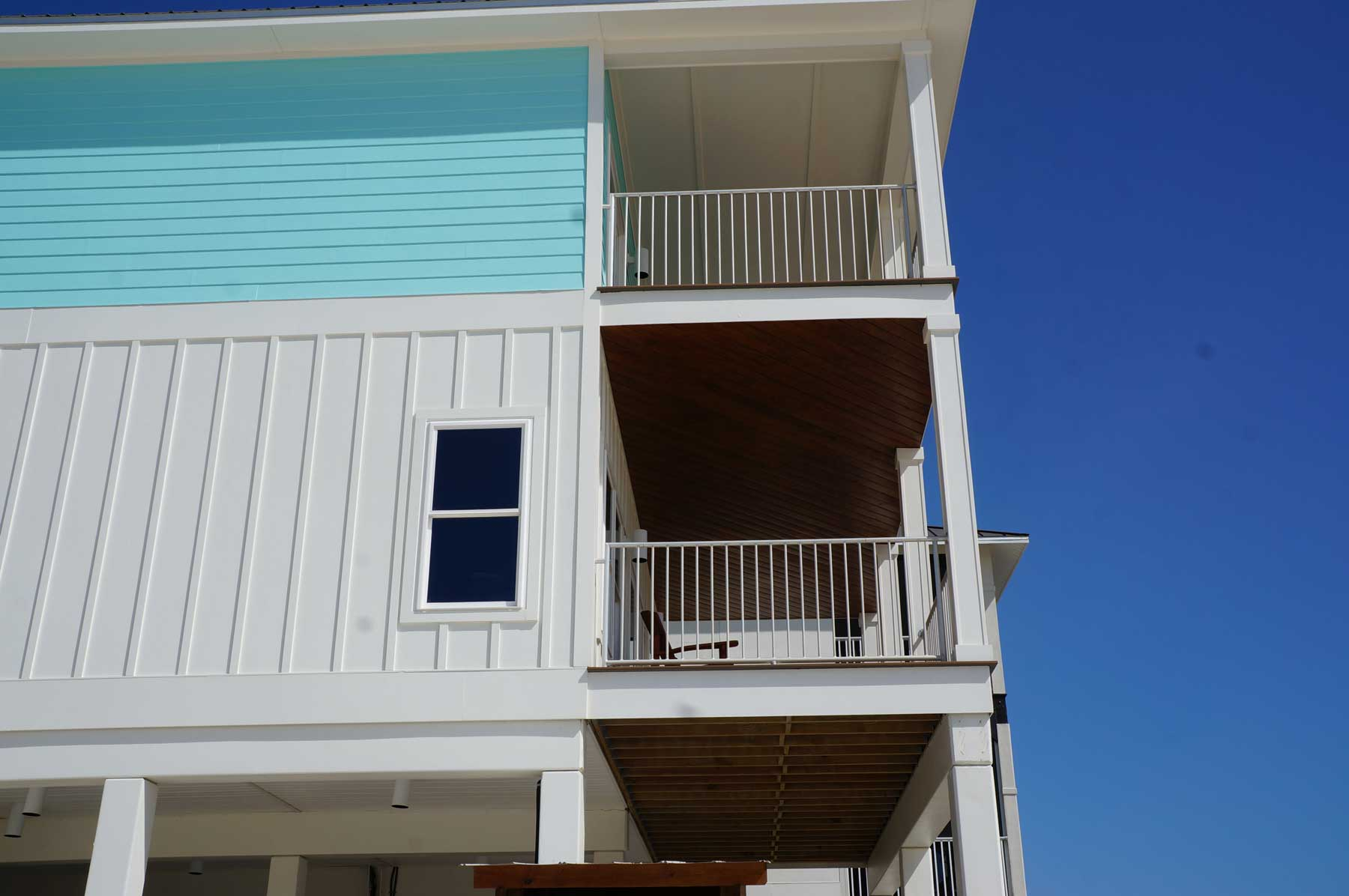 Side yard view of decks on both upper floors. New beach house construction in Mexico Beach, FLA.