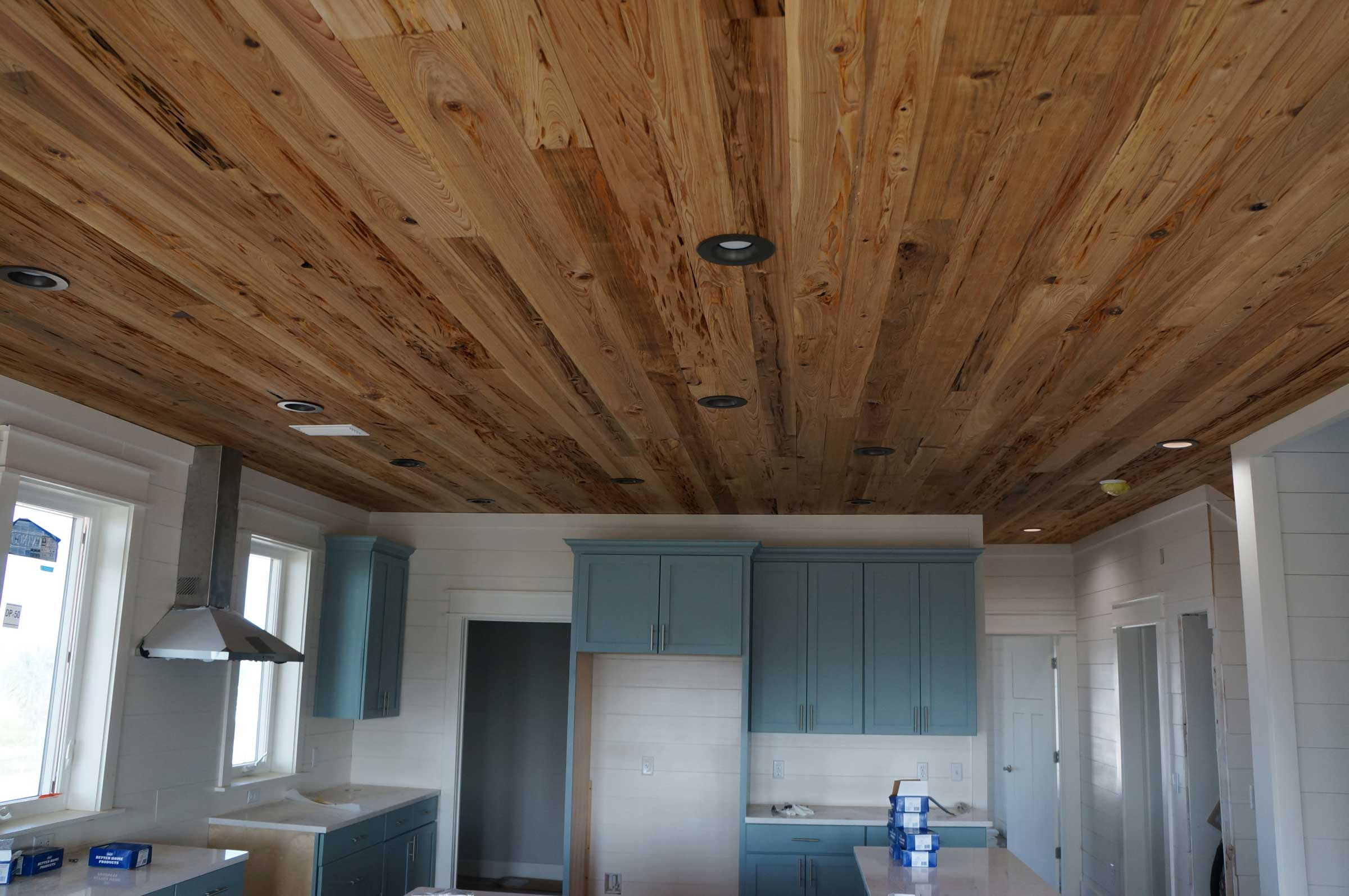 Pot lights in kitchen with unique wood plank ceiling.