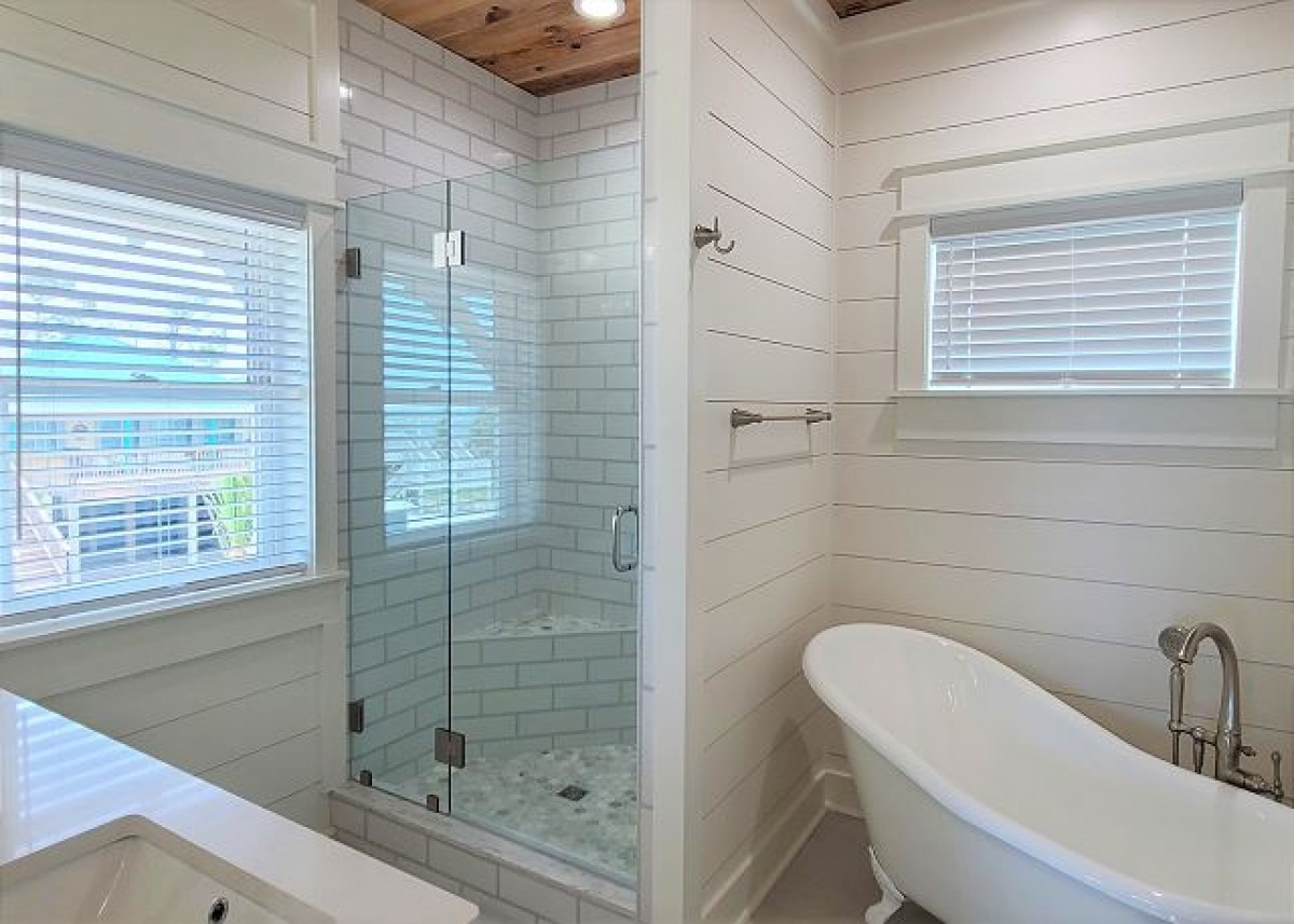 bathroom with tile shower stall and fancy tub