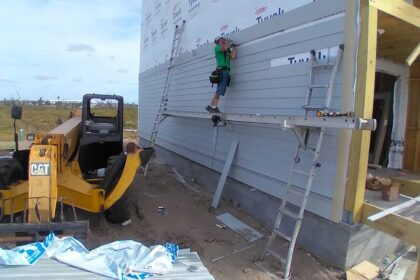 Worker on the exterior side wall of new Mexico Beach home as it's being built.